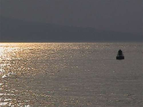 Buoy on sunlit sea