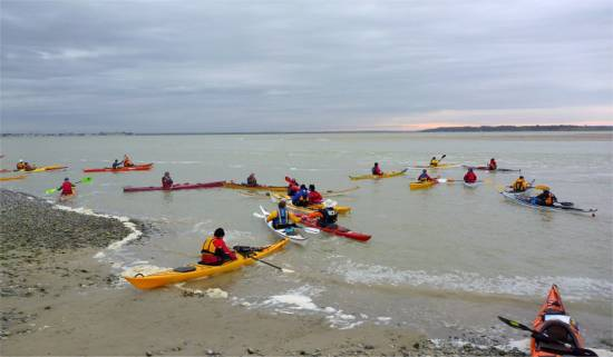 Sea kayakers launching